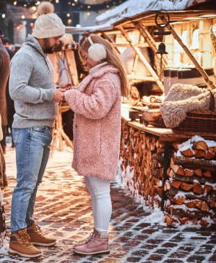 A handsome man and his beautiful girlfriend holding hands, enjoying spending time together, standing at the winter fair at a Christmas time