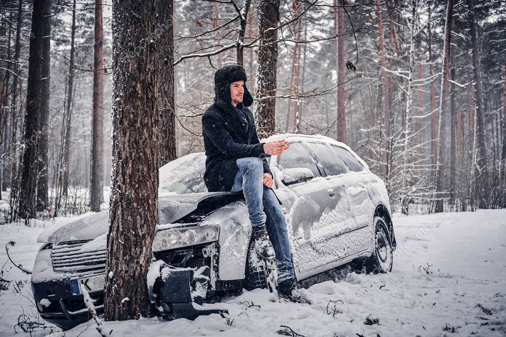 The car got into a skid and crashed into a tree on a snowy road. A driver sits on the bonnet and smokes a cigarette in anticipation of a tow truck