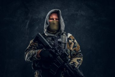 Special forces soldier in military uniform wearing mask and hood holding an assault rifle.