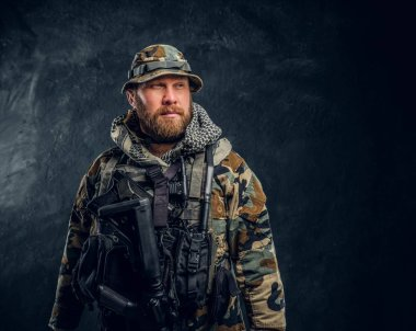 Portrait of a special forces soldier in the military camouflaged uniform, looking sideways.