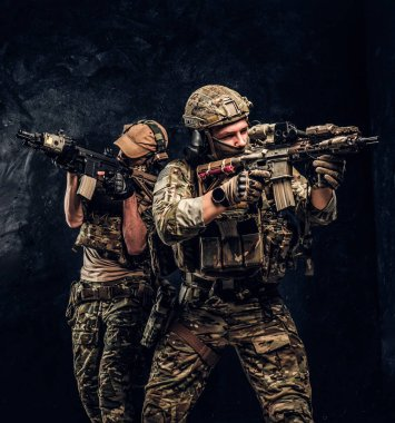 Two special forces soldiers in full protective equipment holding assault rifles and aiming at the targets. Studio photo against a dark textured wall.