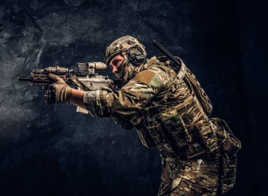 The elite unit, special forces soldier in camouflage uniform holding an assault rifle with a laser sight and aims at the target. Studio photo against a dark wall