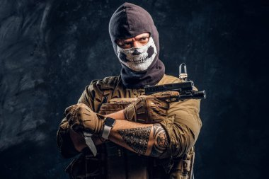 A terrorist in a military uniform and a skull balaclava holding a pistol and a knife and looks at the camera with a menacing look