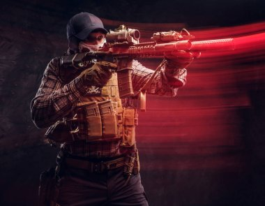 Special forces soldier wearing a checkered shirt and protective equipment holding an assault rifle and aim at the enemy. Red light effect in motion. Studio photo against a dark textured wall stock vector