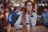 Porträt einer hübschen jungen Frau mit einer Tasse Kaffee