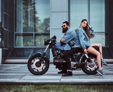 Beautiful interesting couple is sitting onthe bike in denim jacket near glass building. stock vector