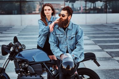 Portrait of attractive couple in denim jackets with motorbike near big glass building at city centre. stock vector