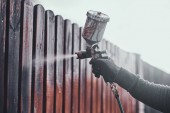 Photo Diligent working is applying colour to the fence with airbrush