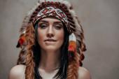 Fotografie Attraktive Frau posiert nackt im Studio mit indischer Federhaube
