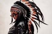 Az amerikai őslakos modell hátulról néz, bőrdzsekit és tollas fejfedőt visel.