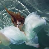 Podvodní dívka. Krásná Rudovláska v bílých šatech, plavání pod vodou