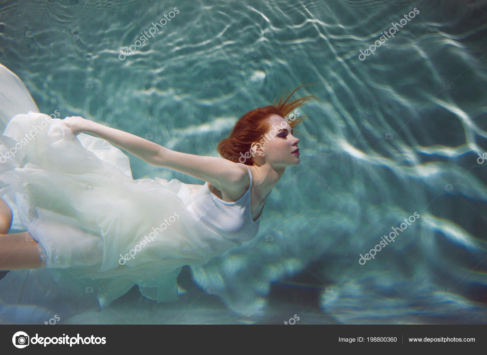 Underwater girl. Beautiful red-haired woman in a white dress, swimming  under water