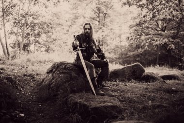 Knight in the forest. Guy in medieval costume with sword. effect of toning