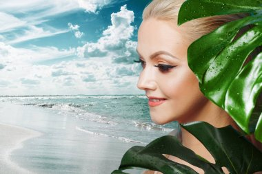 Face of attractive young blonde and leaves of palm trees.