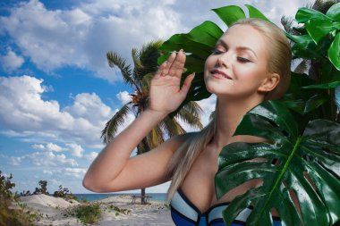 Young woman in blue bikini among palm trees and tropical plants.