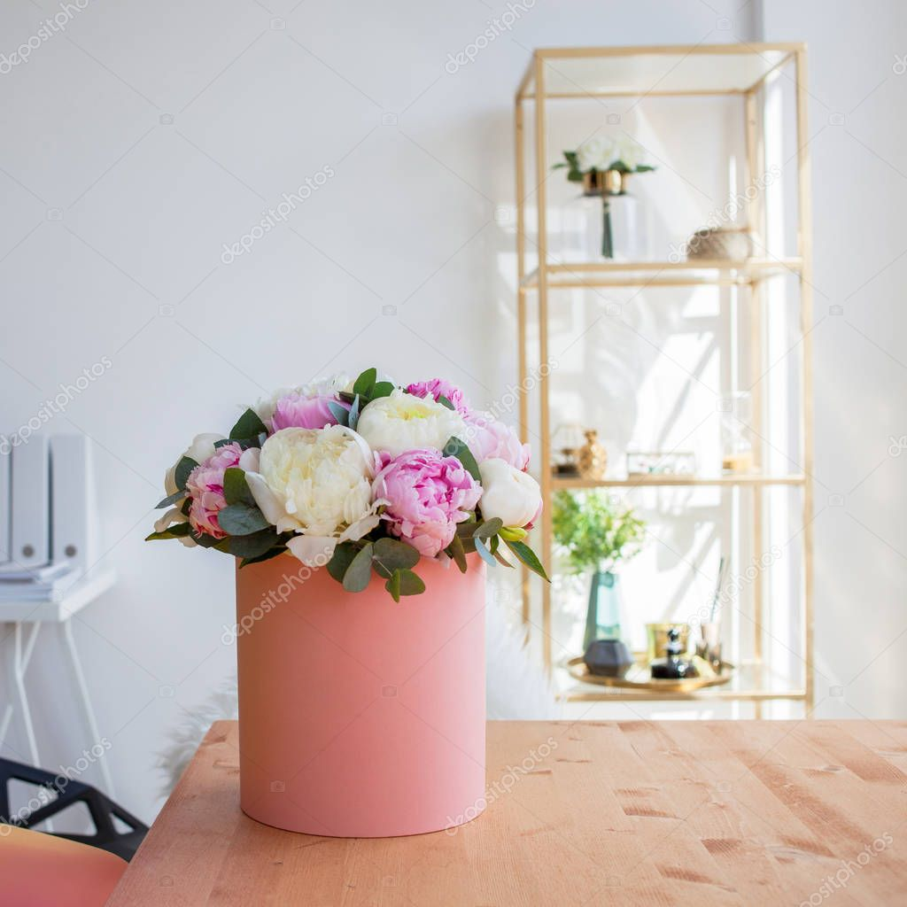Flower delivery to office. Working space, table with notebooks and magazines. Luxurious bouquet of peonies in pink box.