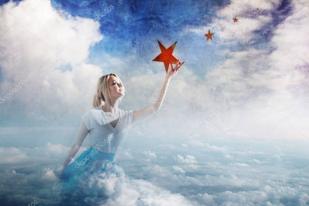 Young attractive woman Sitting on a cloud reaching for the star. Take a star from the sky, dreams and plans, concept