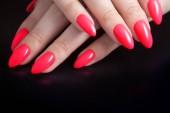 Fotografie Dámské ruce s dokonalou červená manikúra. Lak na nehty červené korálové barvy. Černé pozadí
