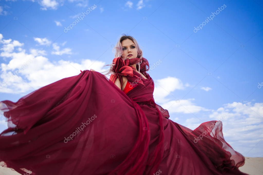 Girl in red. Beautiful young woman in a scarlet dress flying