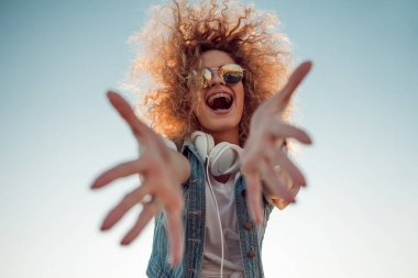 Happy girl pulls her hands into the frame.. Young woman with big headphones.