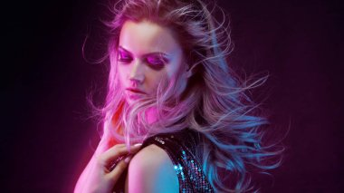 Young attractive blonde woman dancing in club, color light, motion effects