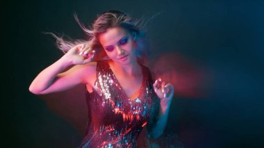 Bright and stylish young woman dancing in club, color light, motion effects