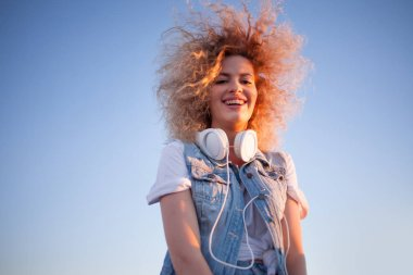 Trendy girl with large headphones on sky background, free space on the right.