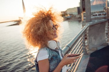 Trendy girl with large headphones and sunglasses on a city walk, young woman uses a smartphone