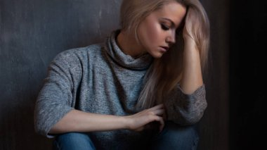 Depressed woman. blonde girl sitting on the floor, sadness and depression
