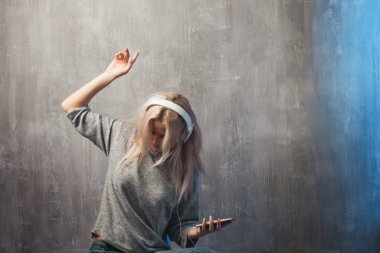 Dancing attractive woman listening to music in the mobile app. Girl music lover.