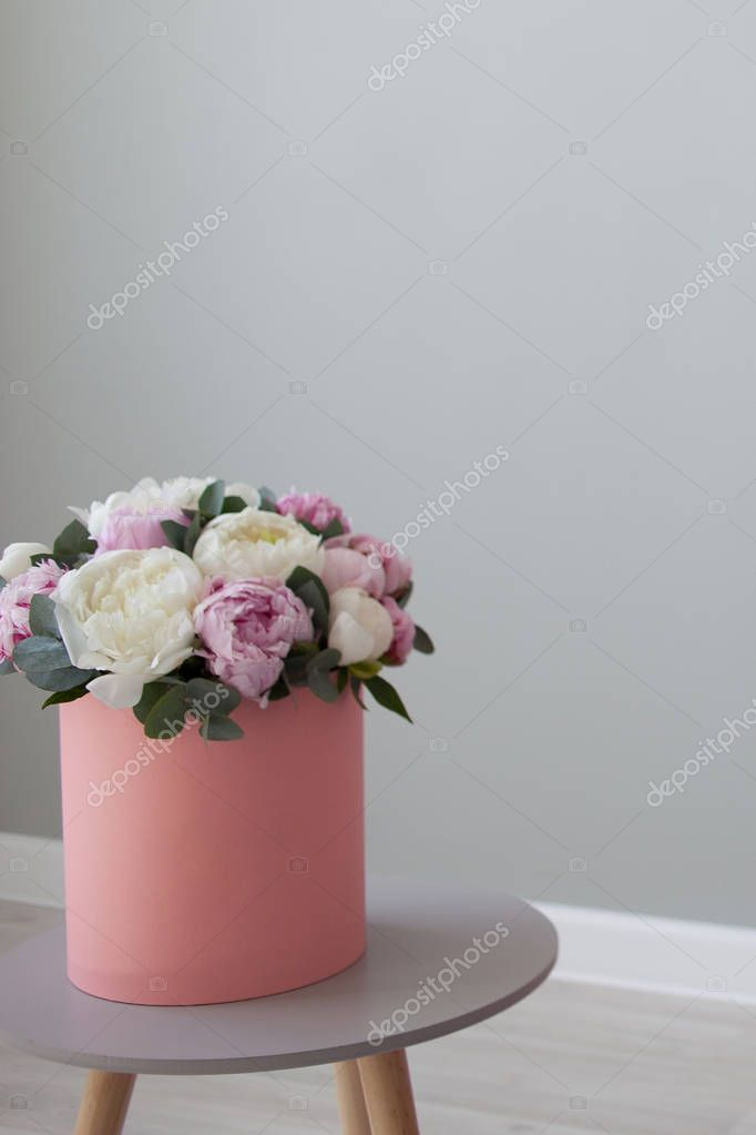 chic bouquet of peonies in a gift hat box. Pink box on light grey background