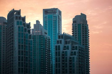 Skyline, skyscrapers in Dubai. Many tall buildings at sunset, silhouettes of skyscrapers