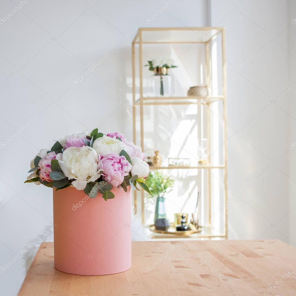 Flower delivery to the office. Working space, table with notebooks and magazines. A luxurious bouquet of peonies