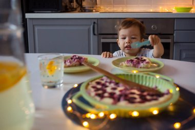 Happy kid reaching for homemade cake. Home kitchen