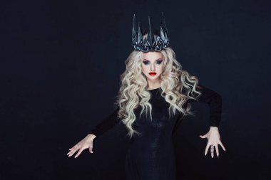 Portrait of a Gothic Princess. Beautiful young blonde woman in metal crown and black cloak.
