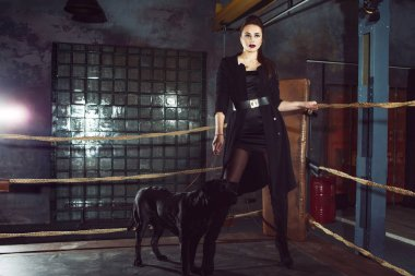 Stylish and sexy woman in black with black Labrador.