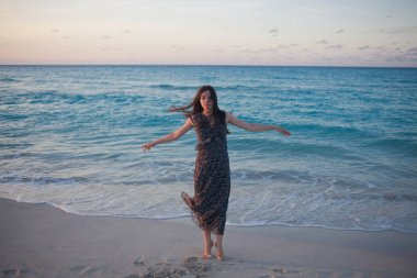 young woman in a long dress walking on the ocean.