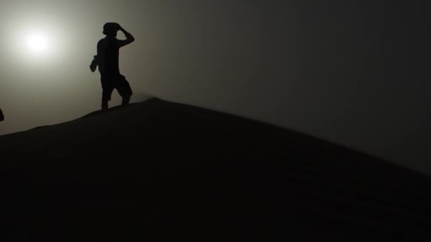 silhouette of a man on top of a dune, desert. Man traveler in a hat, standing on the sand