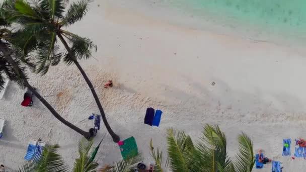 Krásná pláž s bílým pískem palem a průzračným mořem. Lidé opalovat se a plavat