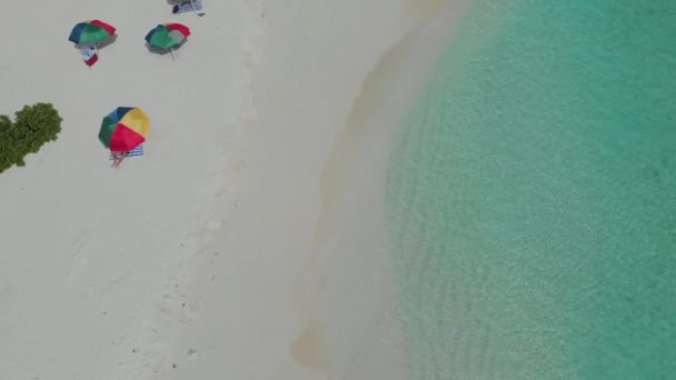 Colorful umbrellas for protection from the sun on the beach. Clear sea and white sand