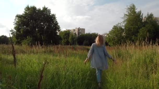 Girl runs across the field. Happy young woman running along