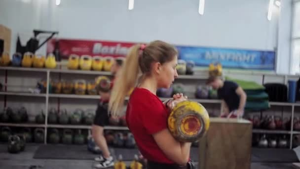 mladá žena atlet provádí roztlačení dlouhý cyklus s kettlebell. Dívka v posilovně fitness a sportovní cvičení s kettlebells