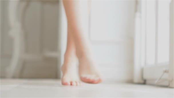 Piedi nudi di donna, parti del corpo. Giovane donna a piedi nudi entra nel telaio