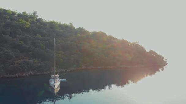 Vitorlás jacht kikötve a parton, egy kellemes tengeri drón videó.