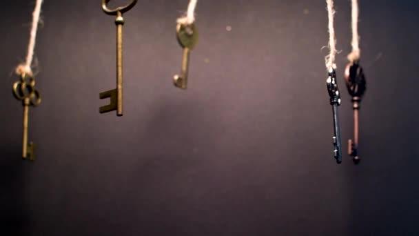 Mnoho různých starých klíčů z různých zámků, visí shora na strunách.