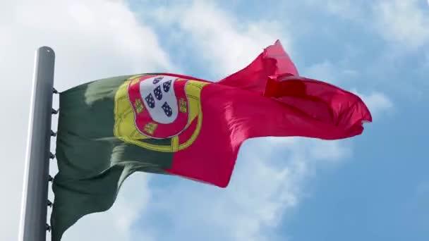 Portugália zászlaja lobogott a szélben. Nemzeti zászló a kék ég ellen,
