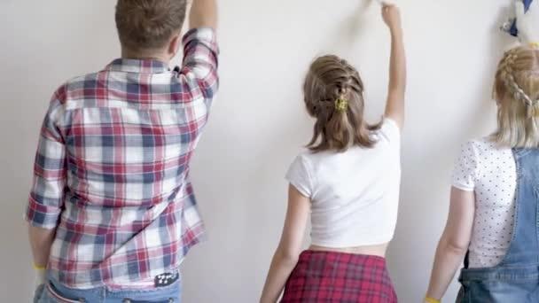 Otec, matka a dcera malba zdí v bytě pokoj. Krásná mladá rodina dělá opravy v novém bytě. Rodiče a dospívající dívka dělat zdobí místnost, směje se a baví