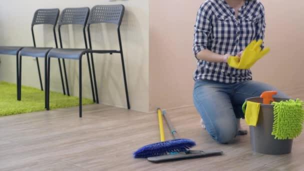 Mladá žena čištění podlahy při pokojové