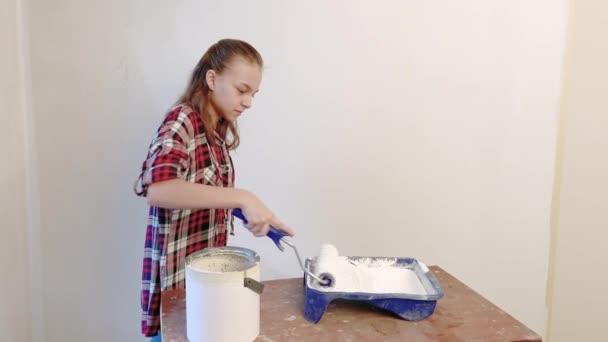 Teenie-Mädchen bemalt Innenwände in der Wohnung mit einem Farbroller. Kind selbst repariert in ihrem Zimmer - bemalt aktiv Wände mit weißer Farbe. Renovierungs- oder Umbaukonzept.