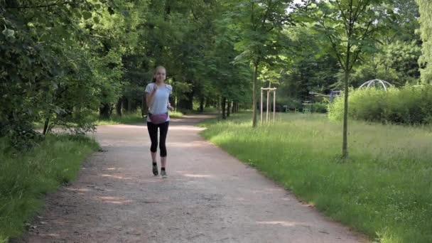 Zeitlupenaufnahme eines Mädchens, das im Sommer im Park läuft. Gesunder Lebensstil. Weibliches Kind mit Kopfhörern, das Musik hört, übt sich in Fitness.